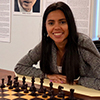 Nadya Ortiz, (MS in CS, 2014) poses behind a chess board.